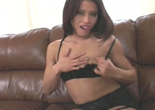 Brunette Milf in black lingerie masturbates her pussy on brown embed